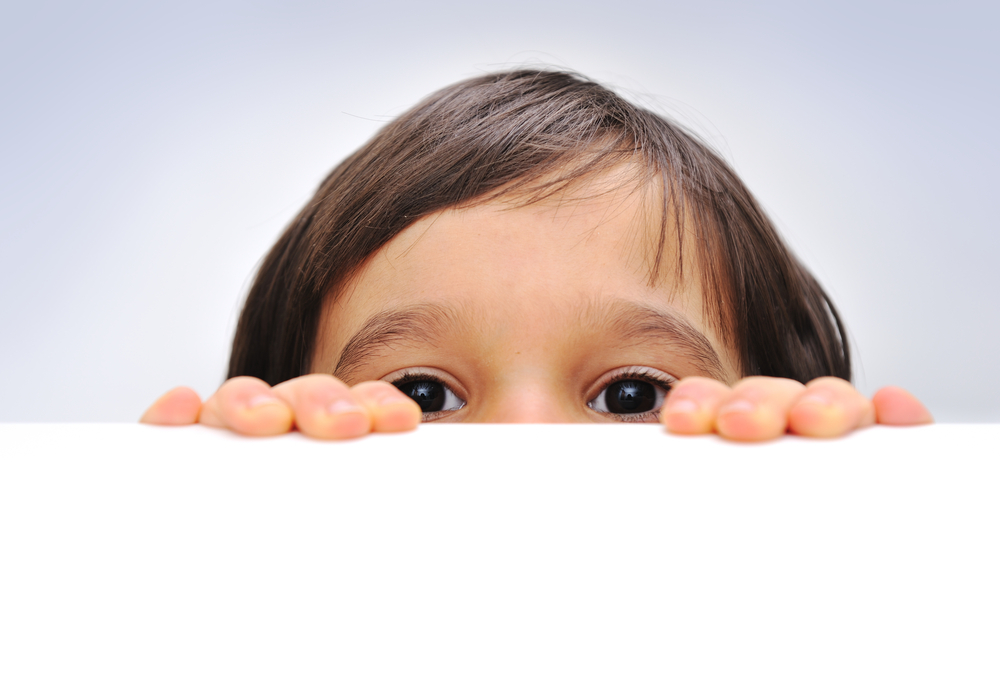 Child holding an empty sign over a white background, hiding behind, copy space