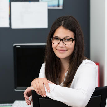 Friendly attractive young businesswoman wearing glasses leaning over the back of her chair at the office to smile at the camera
