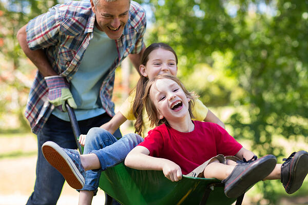 Happy father and his children playing with a wheelbarrow on a sunny day