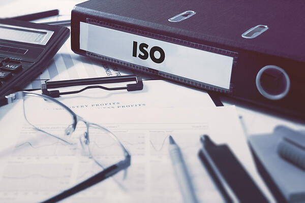 Office folder with inscription ISO - International Organization for Standardization - on Office Desktop with Office Supplies. Business Concept on Blurred Background. Toned Image.