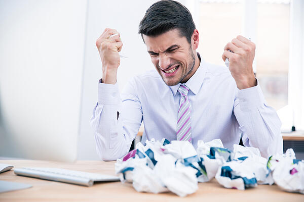 Upset businessman sitting at the table with crumpled paper in office