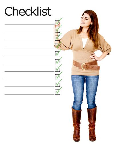 Woman ticking on a checklist - isolated over a white background