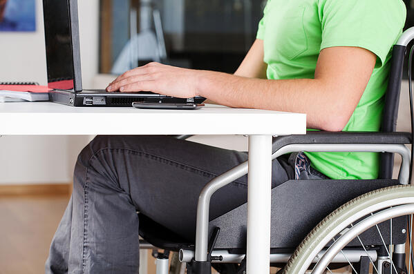 Young man on wheelchair studying in his room