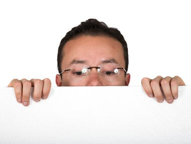 man with glasses peeping over white card over white background