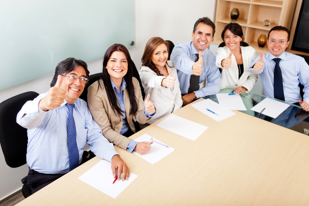 Successful business team in a meeting with thumbs up